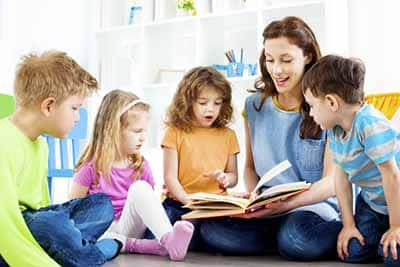 Teacher Working with Kids on Reading Skills