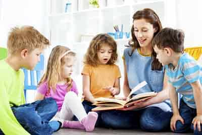 Teacher Working with Kids on Reading