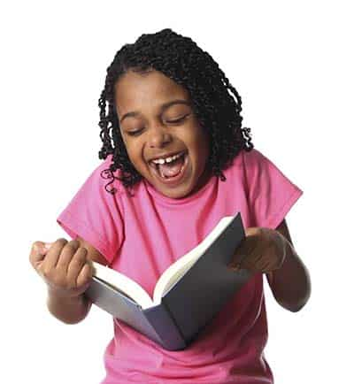 Little girl giggling while reading a funny book